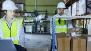 Stock Video Footage of 2 warehouse employees discuss stock and storage requirements