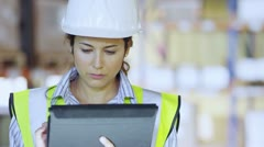 Stock Video Footage of Female warehouse employee is working on a digital tablet and checking inventory