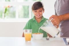 Stock Photo of Father putting milk in the cereal of his son