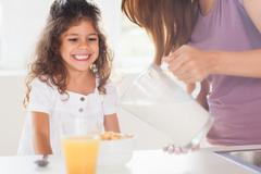 Mother putting milk in the cereal of his daughter - stock photo
