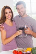 Lovers toasting with a glass of wine and looking camera Stock Photos