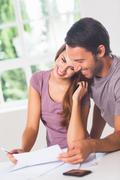 Smiling lovers in front of invoices Stock Photos