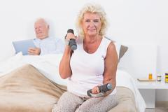 Elderly woman exercising with hand weights - stock photo