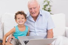 Stock Photo of Grandfather and grandson with a laptop