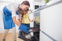Stock Photo of Smiling mother taking cookies out of the oven