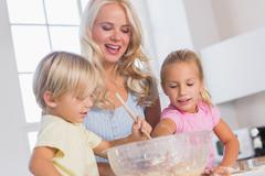 Children mixing the dough bowl with spoon Stock Photos