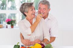 Old man tasting vegetable held by wife Stock Photos