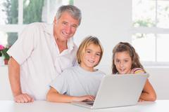 Grandfather and children looking at the camera with laptop in front - stock photo