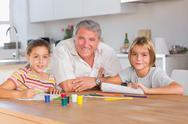Grandfather and her grandchildren smiling at the camera with drawings Stock Photos