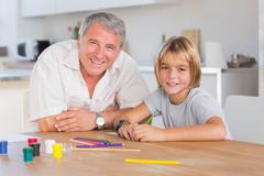 Stock Photo of Grandfather and grandson looking at camera with drawings