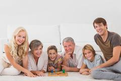 Stock Photo of Family looking at the camera with board games