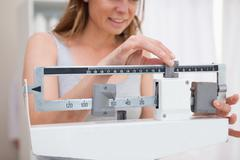 Stock Photo of Woman adjusting scale