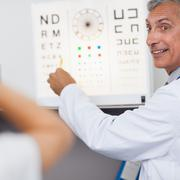 Stock Photo of Doctor smiling while doing an eye test on a patient in a hospital