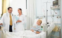 Stock Photo of Pregnant patient in her bed talking with doctors