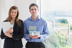 Estate agent holding clipboard and man holding miniature model house Stock Photos