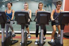Four women working out at spinning class Stock Photos