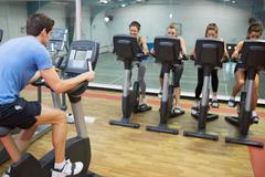Stock Photo of Male instructor teaches spinning class