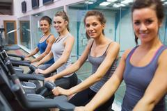Stock Photo of Happy women on exercise bikes