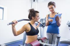 Stock Photo of Trainer with woman on weights machine