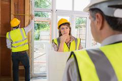 Woman and architect talking while man is measuring wooden frame - stock photo