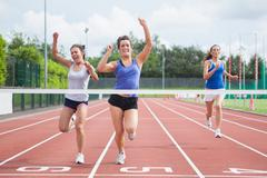 Athletes celebrating as they cross finish line Stock Photos