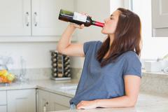 Woman drinking a bottle of wine alone Stock Photos