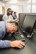 Stock Photo of Man taking nap at computer class
