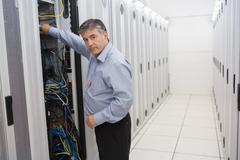 Man fixing wires of servers Stock Photos