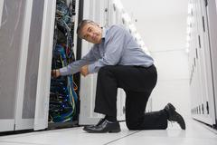 Stock Photo of Man fixing server wires