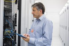 Man using tablet for maintenance on servers Stock Photos