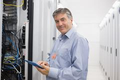 Smiling man doing maintenance on servers Stock Photos