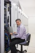 Man working on laptop to check servers Stock Photos