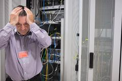 Man looking weary of data servers Stock Photos