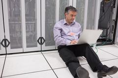 Man sitting on floor using laptop to check the servers Stock Photos