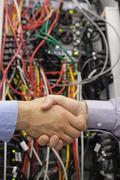 Handshake in front of a data store Stock Photos