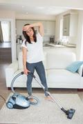Exhausted woman hoovering the living room - stock photo