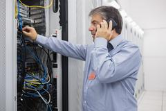 Stock Photo of Technician phoning while repairing the server