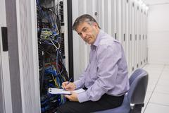 Technician looking up from making notes on server Stock Photos