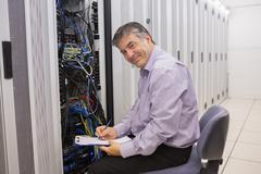 Stock Photo of Happy technician repairing the server