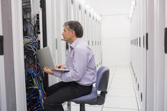 Technician controlling the server with a laptop - stock photo