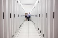 People standing in corridor of data center - stock photo