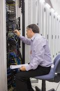 Stock Photo of Technician with a clipboard checking servers