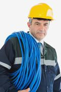 Mature man wearing hardhat with cable - stock photo