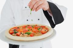 Stock Photo of Chef garnishing pizza