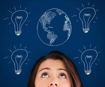Woman standing against a picture of bulbs and globe Stock Photos