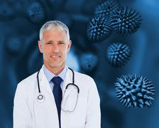 Doctor with stethoscope standing against a background - stock photo