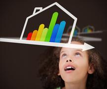 Surprised girl looking up at energy efficient house graphic - stock photo