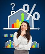 Thinking businesswoman standing against a energy efficient house graphic Stock Photos