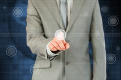 Businessman's finger activating futuristic touchscreen - stock photo