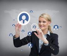 Businesswoman standing before touch screen Stock Photos